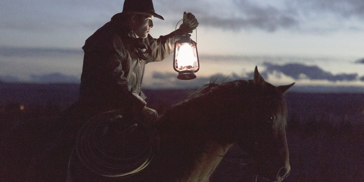 Cowboy riding horse at night carrying lantern