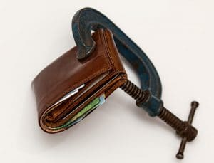 Image of a wallet being squeezed by a clamp